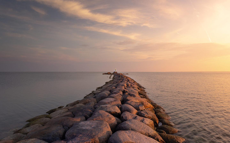 gray rocks pier on body of water